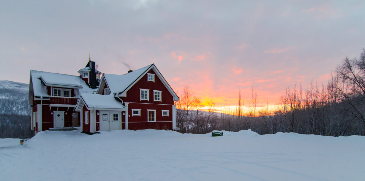 Sunrise behind a traditional Finnish house in the northernmost Village of Utsjoki