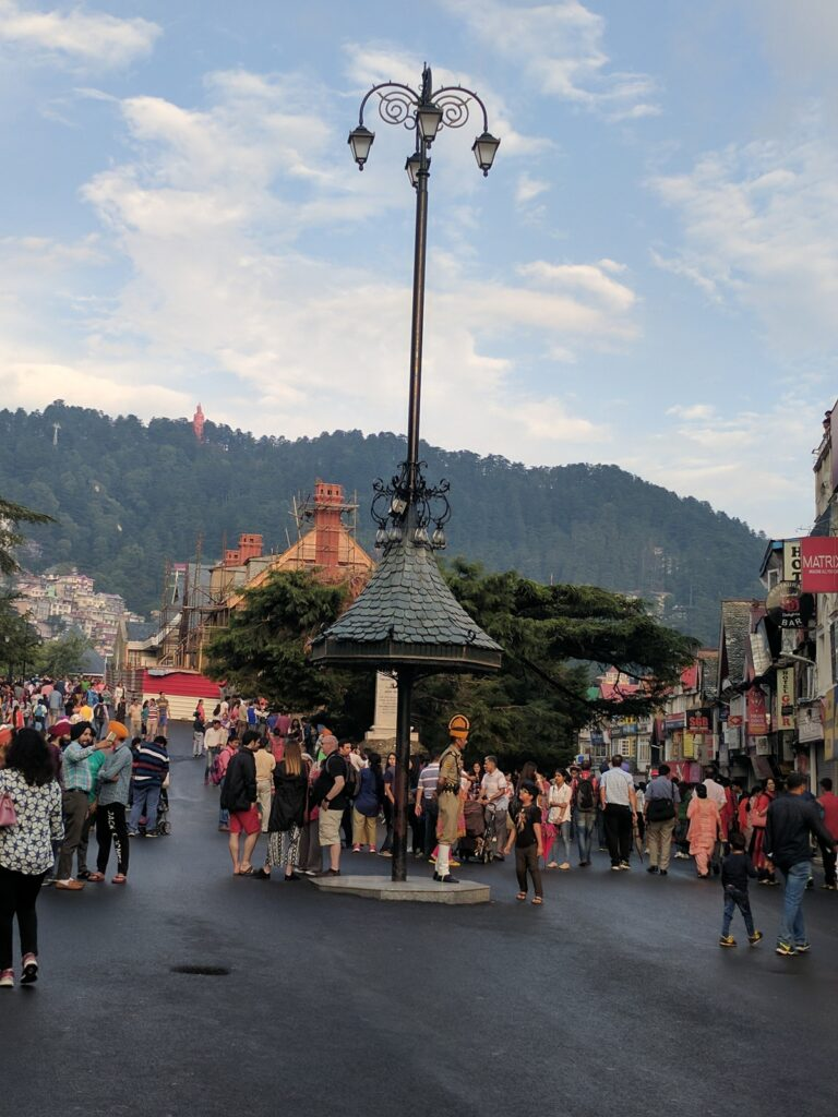 Crossroads with roads leading towards the Mall Road of Shimla, heritage walks and local town. Best views to be found from this spot, notice the traffic policeman in traditional garb, and tourists all around!